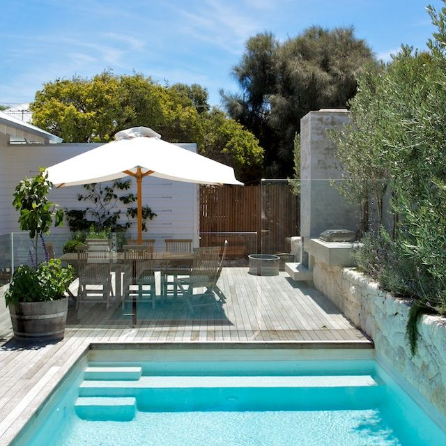 White rendered swimming pool, local limestone raised planter, outdoor fireplace and concrete BBQ bench top. Sorrento house 3. www.marktraversla.com