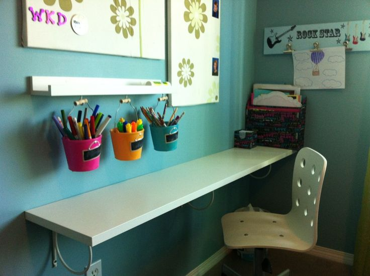 A small workspace created in the corner of a bedroom.  Floating shelf with brackets, hanging buckets for supplies, pull up a chair, and voila!