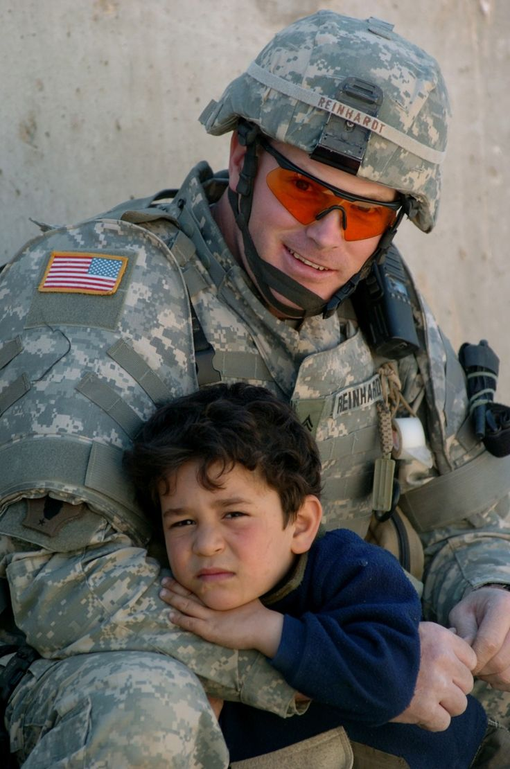 An Iraqi boy rests on the arm of U.S. Army Cpl. James Reinhard outside an Iraqi police department in Baghdad, Iraq