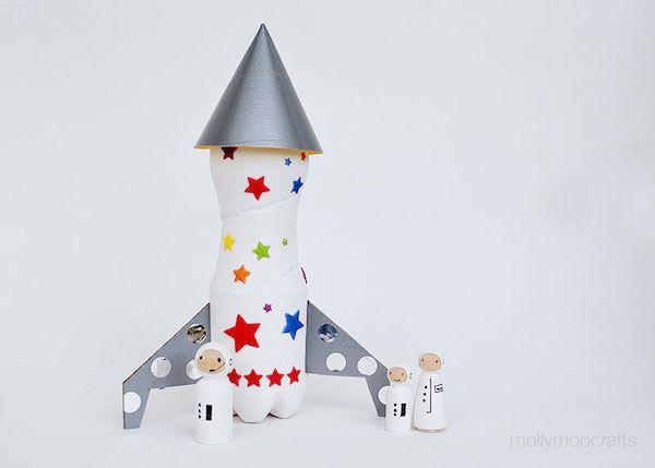"""Manualidades con cohetes espaciales: Pintamos la botella del color deseado, pegamos a los lados dos """"patas"""" de cartón, decoramos con pegatinas de estrellas que podemos comprar en cualquier papelería y para completarlo, pegamos en la punta un cono de cartulina plateada que será la punta del cohete."""