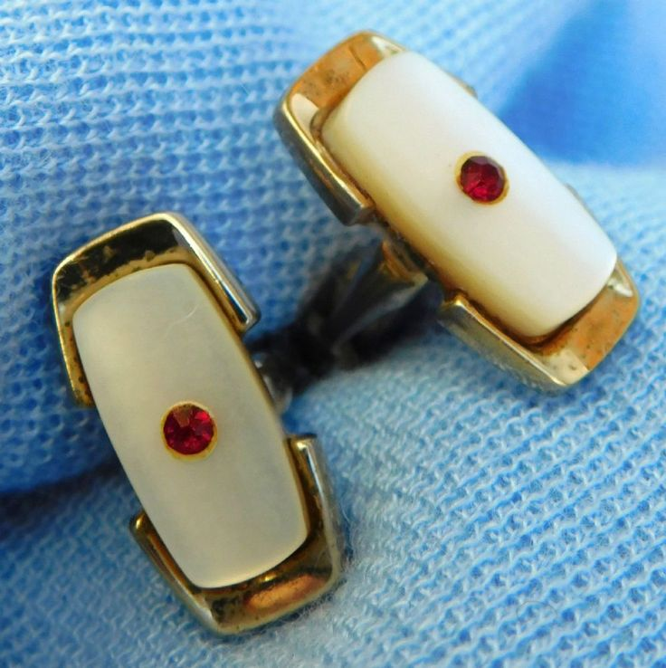 Vintage cufflinks Mother of pearl with tiny red faceted stones in the centre Gold coloured metal These are vintage cufflinks probably made around the
