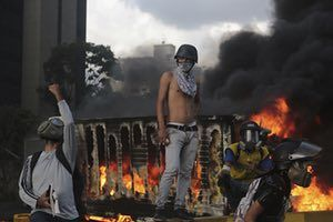 Protesters gather around a traffic barrier during clashes with riot police in Caracas.