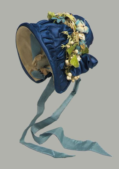 Doll's bonnet, ca 1840 France, the Museum of Fine Arts, Boston    Doll's bonnet of dark blue satin faced with yellow taffeta with light blue ribbon ties, trimmed on top with wreath of artificial flowers, dark blue velvet ribbon, and blonde lace.