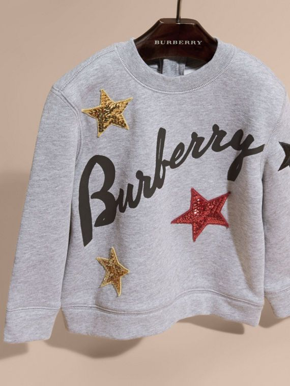 A cotton jersey sweatshirt emblazoned with Burberry lettering and sequined stars. The playful piece is complete with a back zip closure.