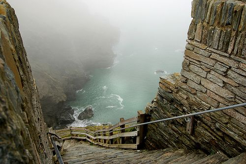 "so beautiful...   ""Tintagel Castle    Tintagel is a village situated on the Atlantic coast of Cornwall, in England, UK.    These precarious steps that hugged the mountainside around Tintagel Castle, the legendary home of King Arthur, were very treacherous.    The mist rolled in from the unforgiving seas and walking on the slate, almost vertical steps, was like stepping onto sheet ice. The steps wound around to a shakey bridge of sorts, for the more intrepid."""