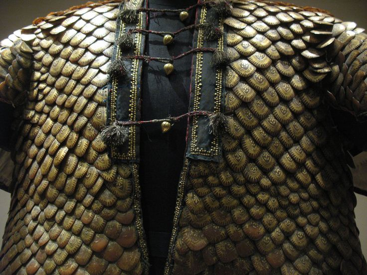 Image 2. Detail. Pangolin scale armoured coat. Indian, Rajasthan, early 19th century. This coat has been covered with the scales of the pangolin or scaly anteater (Manis crassicaudata). The scales have been decorated in gold, and the larger have been used where more protection is required. This is the only known example of this type of armour. It originally had a helmet, also made of pangolin scales, with three plumes.