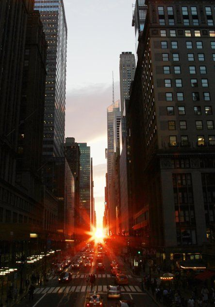 """The sun is seen as it sets between Manhattan buildings on 42nd Street during a phenomenon known as """"Manhattanhenge,"""" Wednesday, July 13, 2011 in New York City. Manhattanhenge, sometimes referred to as the Manhattan Solstice, happens when the setting sun aligns with the east-to-west streets of the main street grid"""