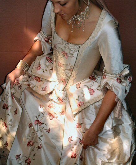 The bodice is ornamented with an eye-catching embroidered and beaded stomacher panel and finishes in a shaped and pleated peplum, embroidered and edged in antique lace. The bodice is laced at the back to achieve a corset-like finish. It has fitted, elbow-length sleeves ending in large, romantic cuffs with lace sleeve flounces. The skirt has an open front to show off the beautiful scrolling floral embroidery and draped panniers, again edged in lace.  Shown in a pale pink embroidered regal…