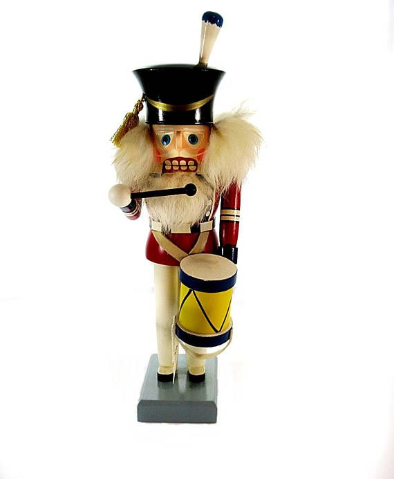 Here is a German made nutcracker handpainted like a old world drummer soldier. He has a wooden plume on his hat and a flag hanging off the drum. It is a Freiberger Raum und Tafelschmuck wooden nutcracker from the Erzgebirge region of Germany. There is fur used for his hair and beard.