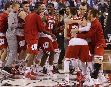 Badgers forward Sam Dekker (second from right) hugs guard Josh Gasser (21) as his teammates celebrate their NCAA Final Four semifinal victory over Kentucky on Saturday at Lucas Oil Stadium in Indianapolis.