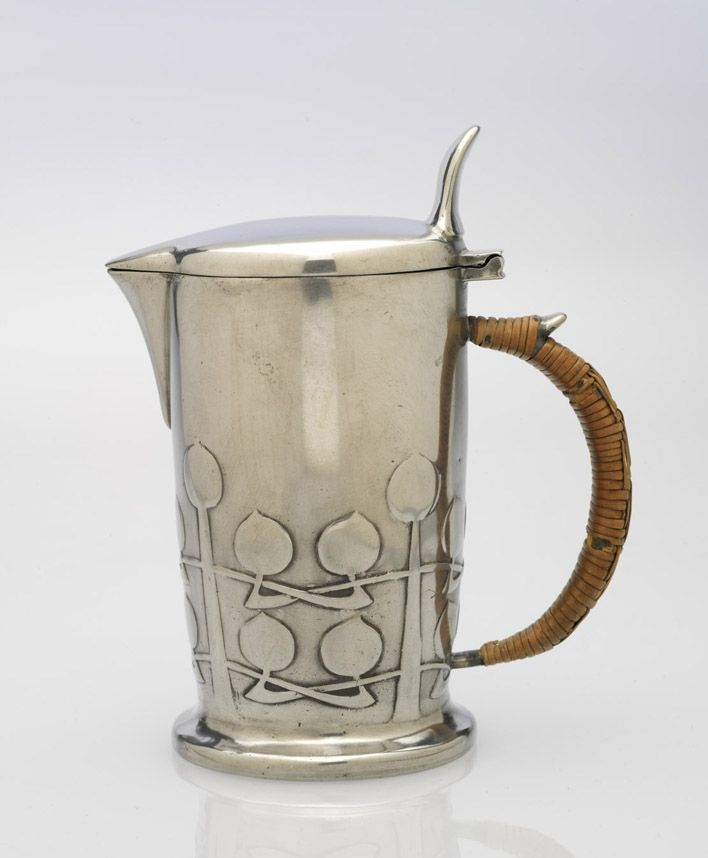 "Archibald Knox (1864-1933) - Made by W. H. Haseler & Co., for Liberty & Co. ""Tudric"" Ewer. Pewter and Rattan. Englan. Circa 1904-1926.  16.5cm x 13.4cm x 7.9cm."