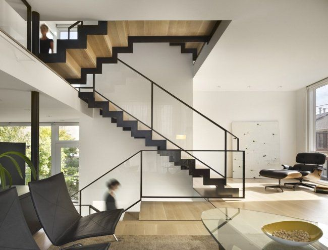 a large wood and metal staircase with glass railings