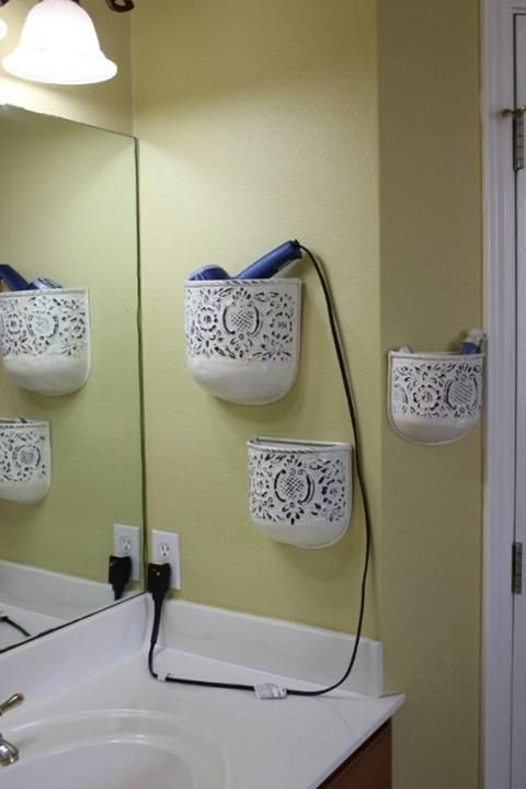 Plant holders make great hair styling supply holders. Instead of hanging plants in them, you just mount them to the wall and put your blow dryer, curling iron and other hair supplies inside. They look great in the bathroom too! >>> Fun way to save on cabinet space!