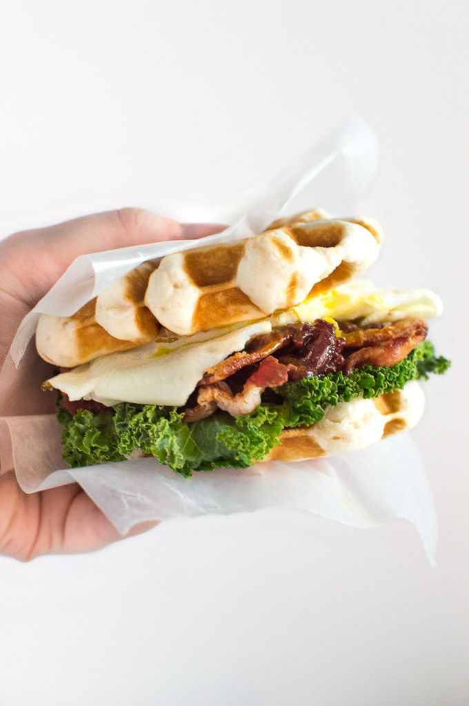 Freshly sizzled bacon, eggs, kale and homemade cherry bacon jam fill this warm Waffle Breakfast Sandwich made from country biscuits. | Crumb Kitchen