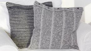 De to strikkede hyggepuder er strikket i lækker blød alpaka, og de lukkes med en række knapper. Den ene pude har et diskret tweedmønster, mens den andens mønster minder om en avis-side.
