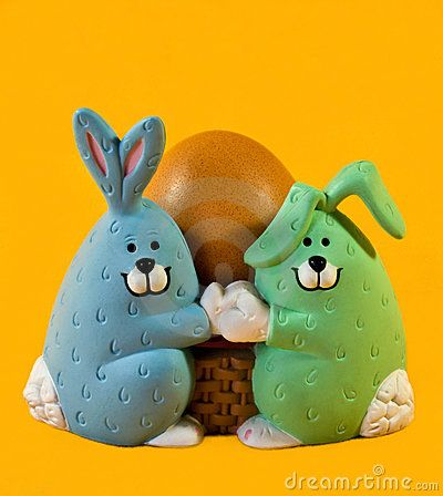 Two ceramic Easter bunnies holding a boiled brown egg