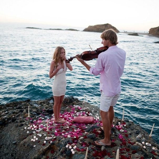 Homem faz pedido de casamento à namorada enquanto toca violino na praia