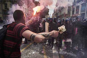A man holds a bouquet of flowers and a torch as he faces riot police during a demonstration in Lyons against the government's planned labour reforms