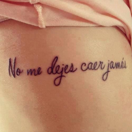 "Little ribs tattoo saying in spanish ""No me dejes caer jamás"", which means ""Do not ever let me fall""."