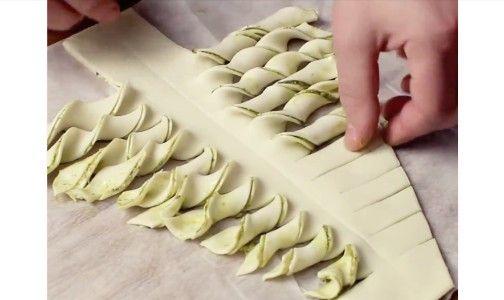 Prende due rotoli di pasta sfoglia e li farcisce con il pesto al basilico. Poi con il coltello traccia la forma di un albero di Natale e taglia delle strisce laterali che poi andrà ad arrotolare. Spennella il tutto con l'uovo ed ecco il risultato!