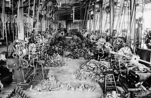 """View of 21"""" and 24"""" lathes on the Willys-Overland Motor Company factory floor. These lathes machined rear axle parts, which are piled at each work station. The lathes are arranged end-to-end, and are attached to rotary belts which are suspended from the ceiling. Natural light is flooding the room from the factory windows.  Check out the link in my profile. Machinistlife.com"""