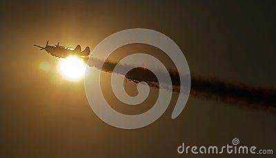 Aircraft show in the sunset sky with smoky long trail.