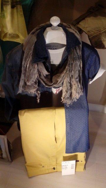 Conjunto formado por camisa tipo tejana manga corta estampada, camiseta blanca con estampado, pantalón color mostaza claro cinco bolsillos, cazadora tejana y foulard de viscosa en colores azules-grises-beig claritos.