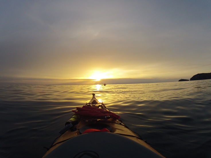 Paddling into the sunset off the coast of Anglesey. South Stack lighthouse can be seen to the right of the photo.