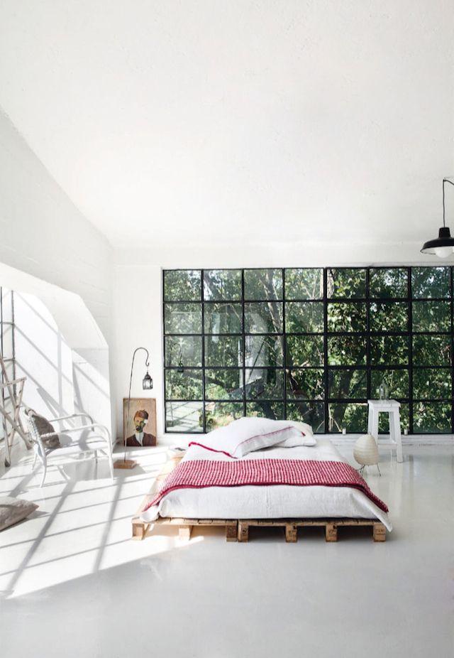 J'aime cette chamber à coucher, si sobre, simple et chic, avec son linge de lit blanc et rouge, et l'utilisation de palettes de bois en guise de sommier. La baie vitrée en fer forgé et la vue qu'elle laisse entrevoir sur la nature luxuriante du jardin est une pièce d'art à elle seule, vous ne trouvez...