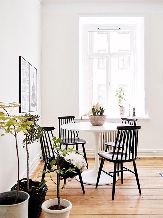 Comedor nórdico y sobrio: mesa circular Tulip y sillas de madera lacadas en negro Windsor