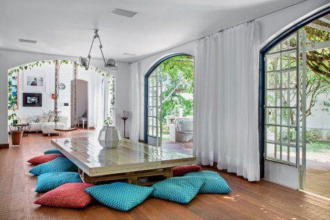Estar integrado: na parede da sala, destaque para os retratos de Tom Jobim e Pixinguinha. Feita sob medida pelo designer holandês Piet Hein Eek, a mesa de jantar foi apoiada sobre caixotes de feira.