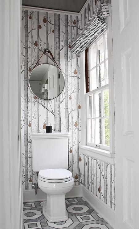 The pears in the uniquely beautiful woods wallpaper from Cole & Sons provides a pop of color to this gray and white water closet as a white porcelain toilet sits below a Keaton wall mirror and on gray and white Walker Zanger Villa D'Oro Palermo hexagon tiled floors.
