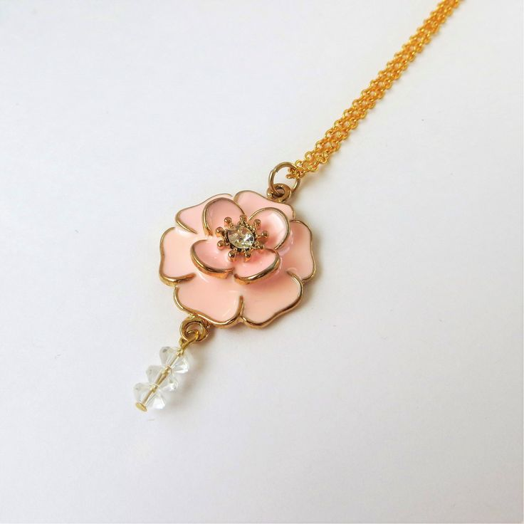Long Gold Necklace with Flower Pendant  This beautiful necklace features a thin gold chain with a pink flower pendant. The flower pendant is edged in gold with a set of clear faceted glass beads dangling beneath.
