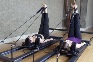 Two woman doing leg exercises on pilates reformer machines. Rear angle view with legs straight up. Click below for more in this series plus my other working out and staying fit images: - Eliza Snow/E+/Getty Images