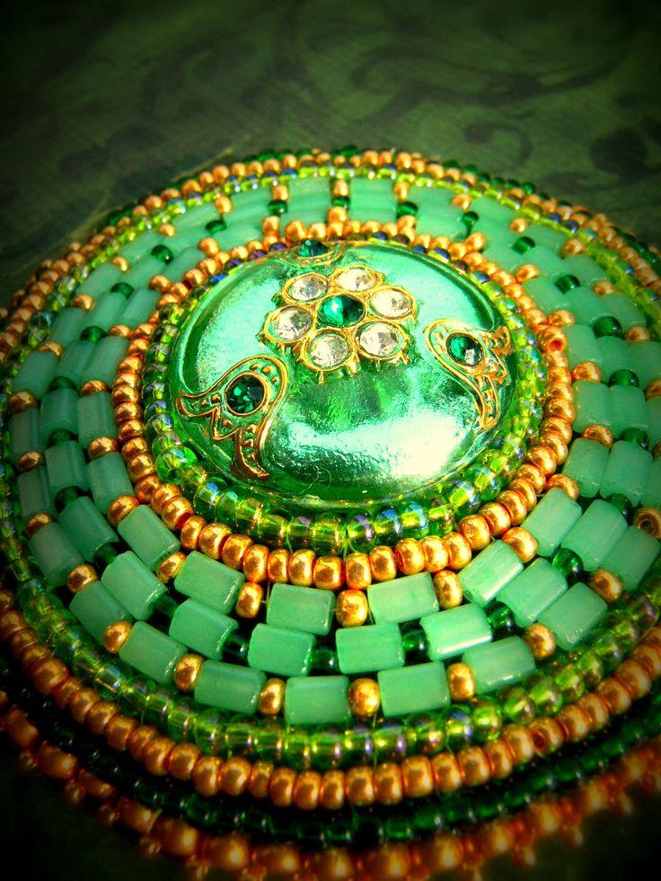 Green Target ..velká vyšívaná brož, starožitný měňavý vitrail - štrasový knoflík je pevně přilepen na filcu zelené barvy, obšit je českým rokajlem a korálky ve zlatých a zelených odstínech.... zapínání je na brožový můstek starobronzové barvy.. podšito zeleným japonským brokátem.. průměr brože je 9 cm, průměr knoflíku jsou 3,5 cm