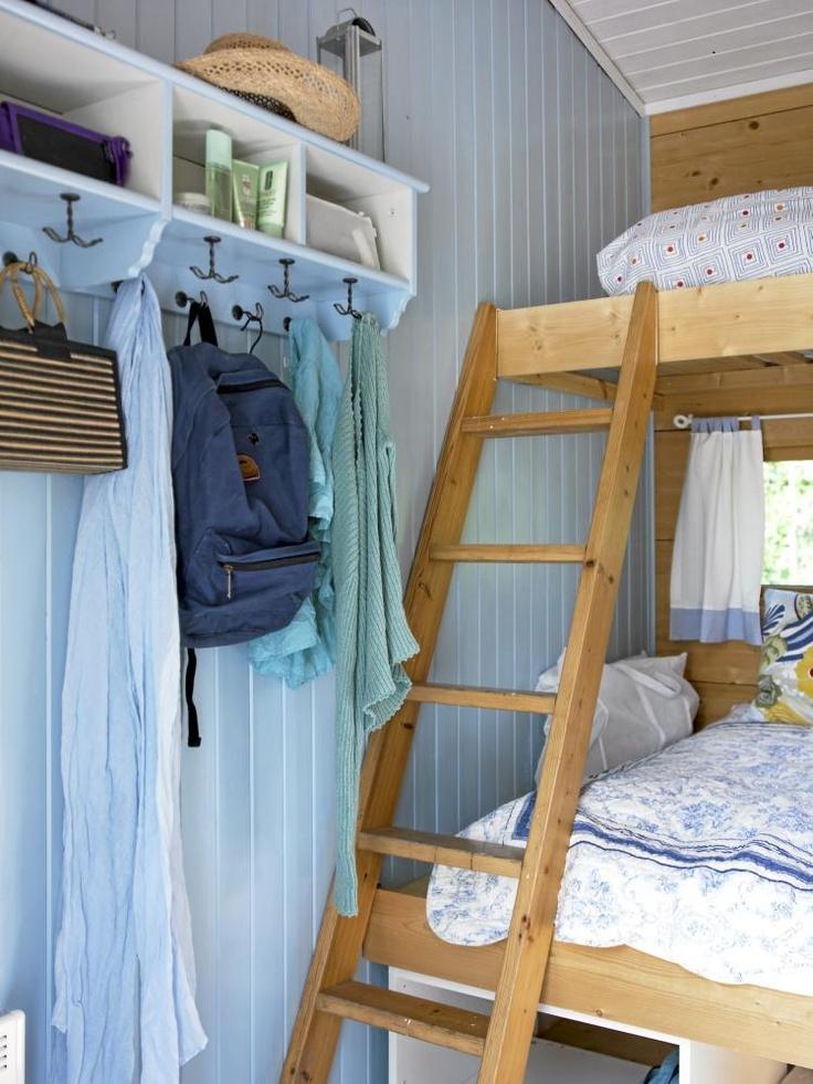 Køyesenger er en enkel og smart løsning som øker antall sengeplasser, uten å stjele for mye av gulvarealet. Her er naturlige trefarger kombinert med en lys blå vegg og hvitt tak.