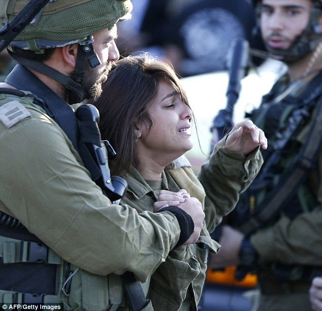 Grief: Pictures show the moment a female Israeli soldier broke down in tears after a comrade was knifed to death at a West Bank petrol station on the same day the two Palestinian girls attacked a pensioner
