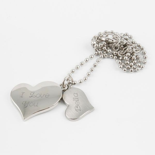 """Double Heart Necklace - Feel the love with our double heart necklace. A smaller brushed silver heart sits atop a larger shiny silver heart. Make this necklace uniquely hers by engraving her name, both of your names or even a simple """"I love you."""""""