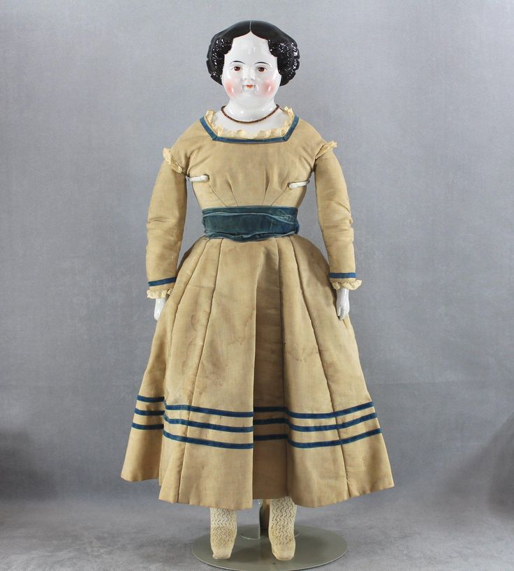 Civil War Era china head doll with brown eyes and high glaze, entirely antique, 26 tall, circa 1860s. The exquisite china shoulder head is clearly the