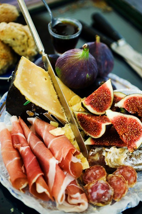 Carnes defumadas - presunto cru e salame. Ao lado dos figos, temos um queijo parmesão de casca preta. Bistrô Cozinhando Com Amigos