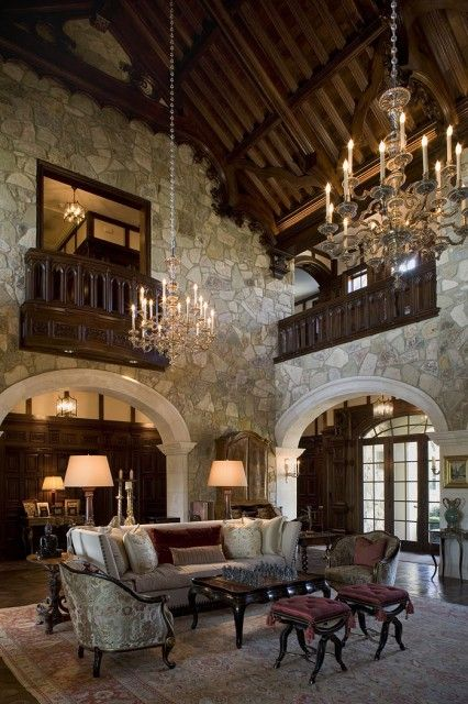 A breathtaking living room, done in a formal Tudor style, with a steeply pitched vaulted wood ceiling and rustic stone walls  (viaInterior Designer -Mark Cravotta)