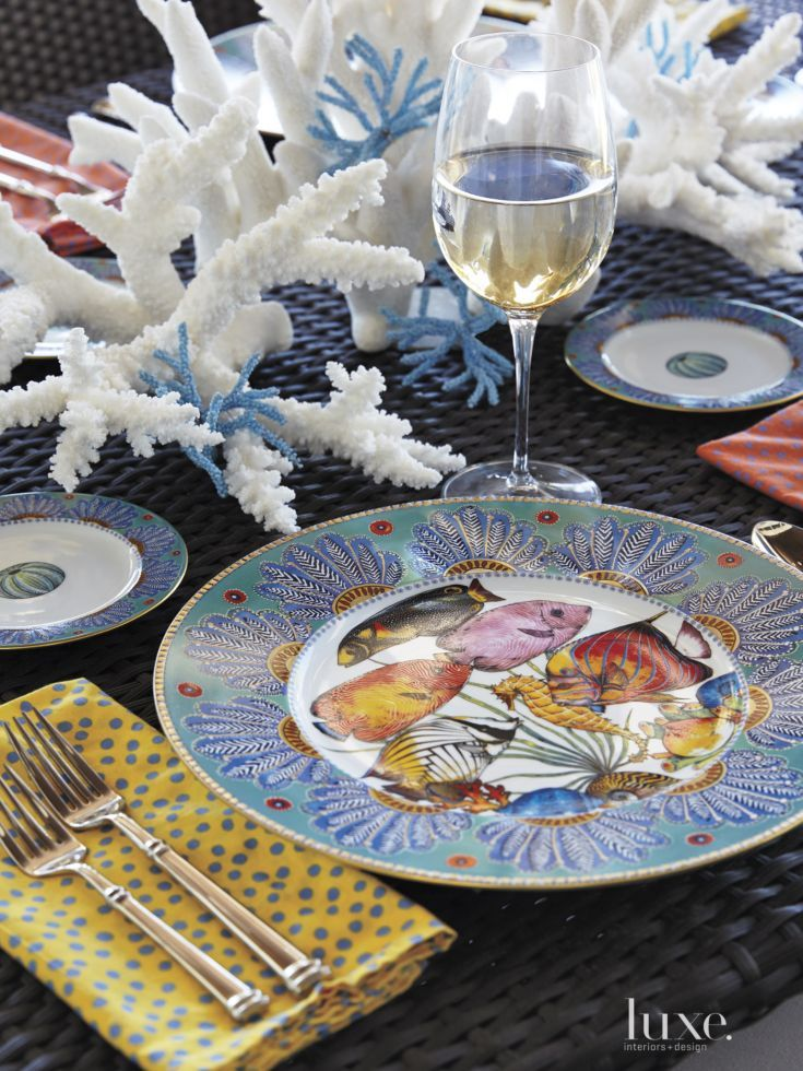 Subtle aquatic notes abound, even down to the brightly colored tropical fish on Penelope Penzo's tableware, which decorates a Gloster dining table on the lanai.