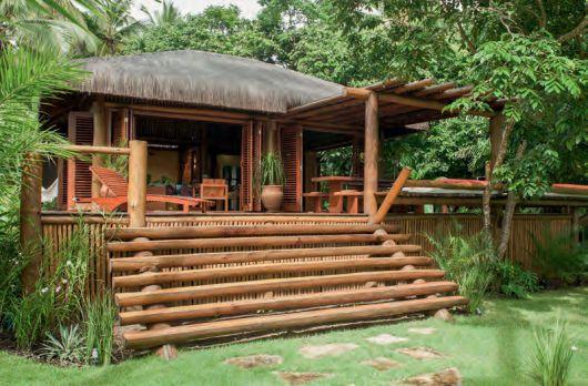 O chalé sofisticado é lindo e cheio de detalhes que enriquecem o visual, como: Escada de meio tronco; Modelo de porta camarão veneziana; Telhado com cobertura de sapé.