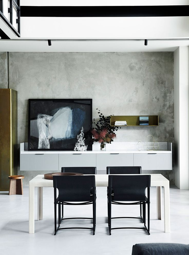 Pale grey polished concrete floor, concrete-look grey painted wall, custom grey panelled joinery with marble benchtop, white rectangular dining table with black chairs, dark abstract art (painting)