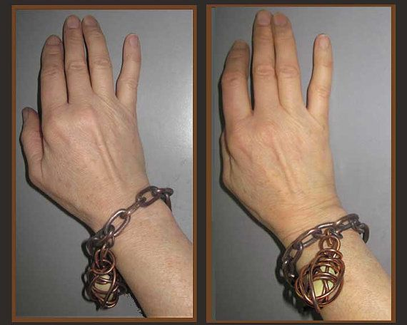 This is an artistic and interesting bracelet, though admittedly some might find it awkward to wear. Made of heavy gauge copper links, with a big toggle clasp, the focal point is a big coiled copper charm enclosing a green pebble. The charm is also weighty, and depending on how it is worn, it either hangs down from the wrist or rests on top or to the side (see photos)  The bright copper pendant stands out against the variegated, darker patina of the bracelet.  Definitely a conversation piece…