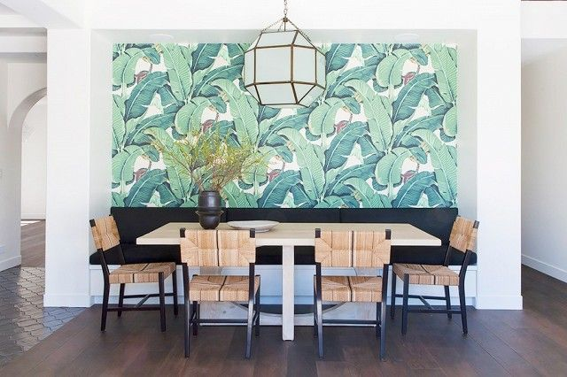 Dining room with tropical wallpaper, a geometric pendant light, and a woven dining chairs