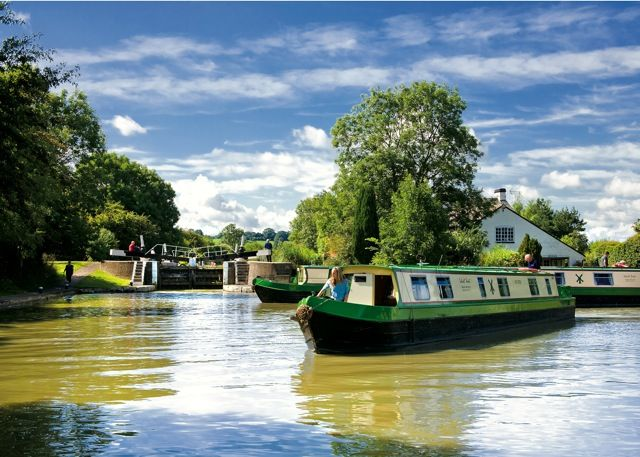 The main wharf at Calcutt Boats. One of our narrowboat hire fleet sets off on a holiday cruise down the Grand Union Canal.
