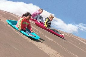 Great Sand Dunes National Park, Colorado. Highest sand dunes in North America. Kids Sledding on Sand