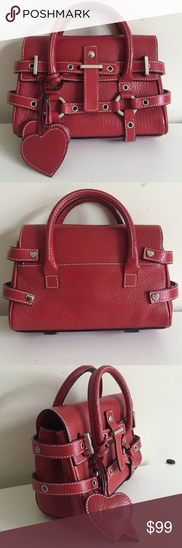 "Auth Luella Bartley Red Baby Giselle Gently used authentic Luella Bartley Baby Giselle in red leather / silver tone hardware / two Luella logo heart shaped charms in red leather / one interior zippered pocket / top flap closure secured with straps / no scuff marks / one minor scratch on the back (3/8"") / 9"" wide x 6"" high x 3.5"" deep (bottom) 2"" deep (top) / comes with care card and pink dust bag / please check my closet for Rebecca Minkoff bags and more / reasonable offers welcome Luella…"