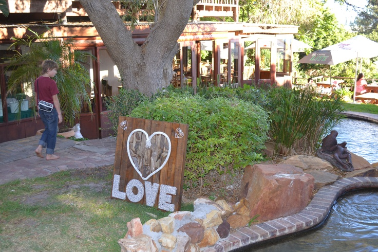 """Our """"Love"""" sign we had made up for the reception where guests can have their photos taken. Heart shape made up of drift wood from the beach, love words covered with sea shells"""